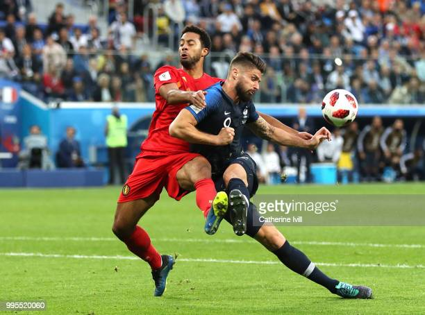 Olivier Giroud of France misses a shot under pressure from Mossua Dembele of Belgium during the 2018 FIFA World Cup Russia Semi Final match between...