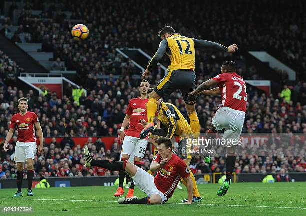 Olivier Giroud scores a goal for Arsenal under pressure from Phil Jones and Antonio Valencia of Manchester United during the Premier League match...