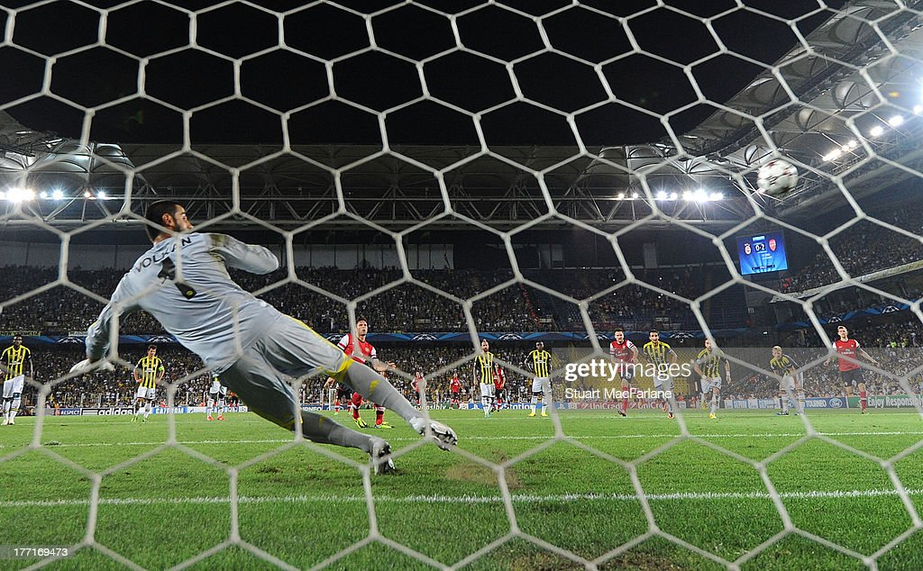 Olivier Giroud shoots past Fenerbache goalkpper Volkan Demirel from the penalty spot to score the 3rd Arsenal goal during the UEFA Champions League Play Off first leg match between Fenerbache SK and Arsenal FC at sukru Saracoglu Stadium on August 21, 2013 in Istanbul, Turkey.