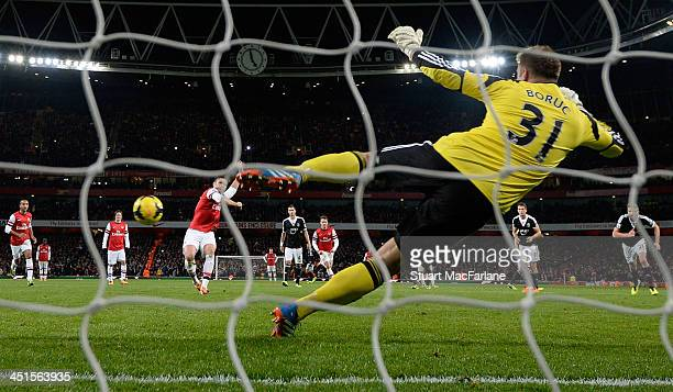 Olivier Giroud shoots past Southampton goalkeeper Artur Boruc to score the 2nd Arsenal goal during the match at Emirates Stadium on November 23 2013...