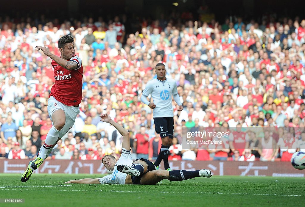 Olivier Giroud shoots past Tottenham goalkeeper Hugo Lloris to score for Arsenal during the Barclays Premier League match between Arsenal and Tottenham Hotspur at Emirates Stadium on September 01, 2013 in London, England.