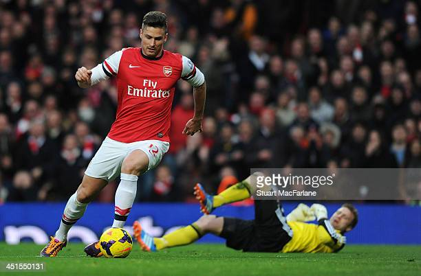 Olivier Giroud tackles Southampton goalkeeper Artur Boruc to score for Arsenal during the match at Emirates Stadium on November 23 2013 in London...