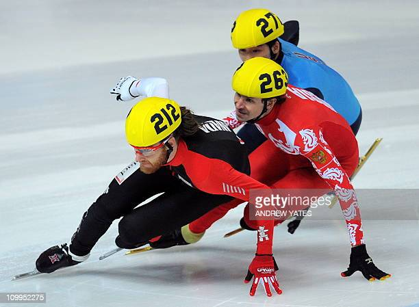 Olivier Jean of Canada competes with Sergey Prankevitch of Russia and Simon Cho of the US during the mens 1500m heats of the World Short Track Speed...