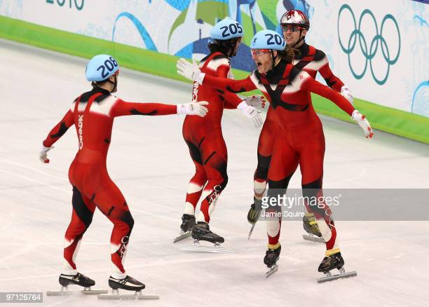 Olivier Jean of Canada leads the celebrations with Charles Hamelin Francois Hamelin and FrancoisLouis Tremblay after Canada won the gold medal in the...