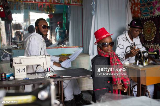 Olivier Kombe a Sapeur with his son inside one of their clothing shops on February 12 2017 in Kinshasa DRC The word Sapeur comes from SAPE a French...
