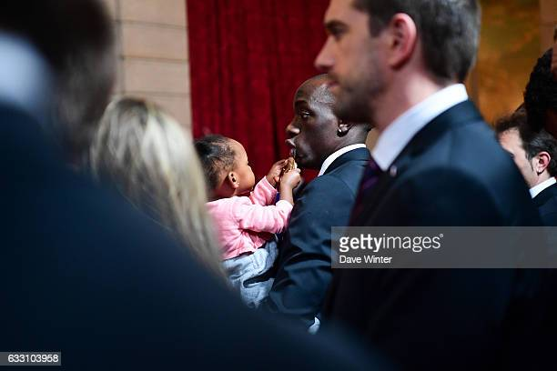 Olivier Nyokas of the France handball team who have just won the World Championships plays with his daughter during a reception given by French...
