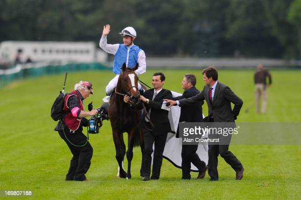 Olivier Peslier riding Intello celebrates winning The Prix du Jockey Club at Chantilly racecourse on June 02 2013 in Chantilly France