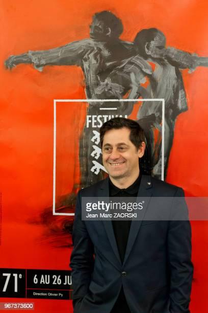 Olivier Py dramaturge comédien réalisateur et metteur en scène français directeur du Festival d'Avignon devant l'affiche élaborée par Ronan Barrot...