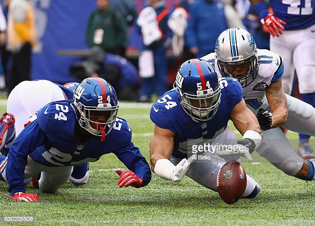 Olivier Vernon of the New York Giants and teammate Eli Apple look to recover a fumble in the second half against the Detroit Lions at MetLife Stadium...