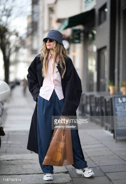 Olja Ryzevski wearing COS cap Jacquemus coat Shirt Jil Sander via netaporter Pants via thefrankieshop sunglasses rayban on March 19 2019 in Berlin...