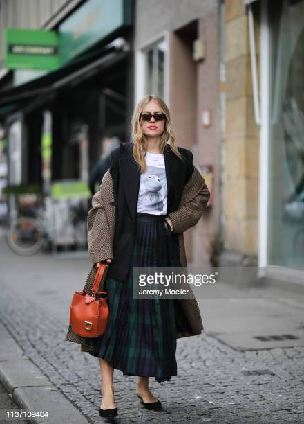 Olja Ryzevski wearing Tshirt Skirt and blazer von Sandro Paris Shoes Jacquemus via Luisaviaroma Coat Andersson Bell Sunglasses acetate Bag Danse...