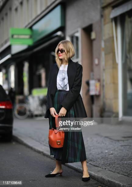 Olja Ryzevski wearing T-shirt, Skirt and blazer von Sandro Paris, Shoes Jacquemus via Luisaviaroma, Coat Andersson Bell, Sunglasses ace&tate, Bag...