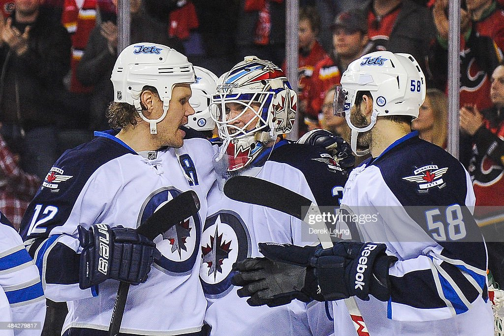 Olli Jokinen #12, Michael Hutchinson #34, and Eric O'Dell #58 of the Winnipeg Jets celebrate after defeating the Calgary Flames during an NHL game at Scotiabank Saddledome on April 11, 2014 in Calgary, Alberta, Canada. The Jets defeated the Flames 5-3.