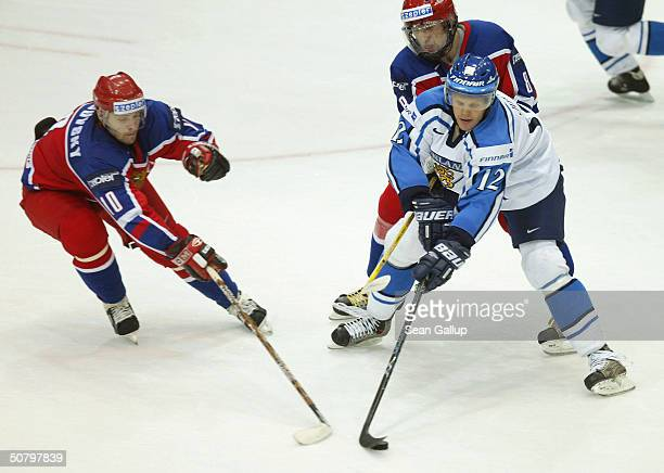 Olli Jokinen of Finland fights for the puck against Oleg Tverdovsky and Alexander Ovechkin of Russia in the Group F qualifier match at the...