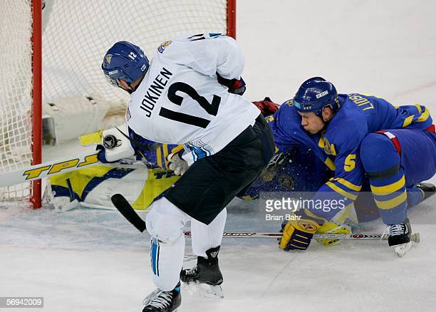 Olli Jokinen of Finland tries to take a shot on goal in front of Nicklas Lidstrom of Sweden during the final of the men's ice hockey match between...