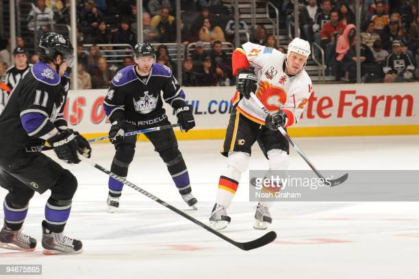 Olli Jokinen of the Calgary Flames passes against Anze Kopitar of the Los Angeles Kings at Staples Center on November 21, 2009 in Los Angeles,...
