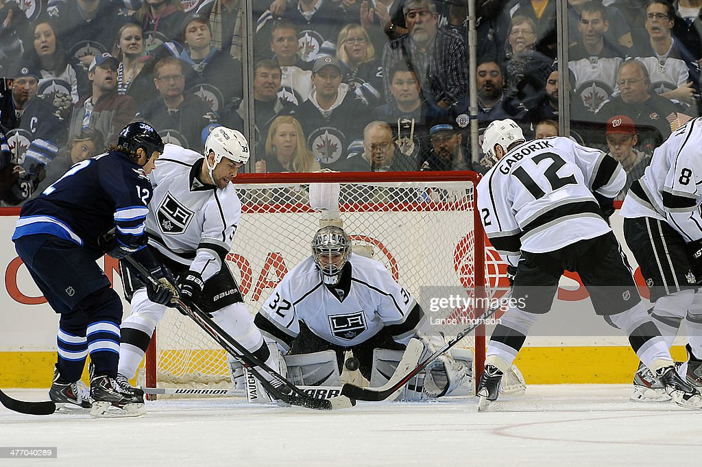 Olli Jokinen #12 of the Winnipeg Jets battles Willie Mitchell #33 and Marian Gaborik #12 of the Los Angeles Kings for the loose puck in front of goaltender Jonathan Quick #32 during third period action at the MTS Centre on March 6, 2014 in Winnipeg, Manitoba, Canada.