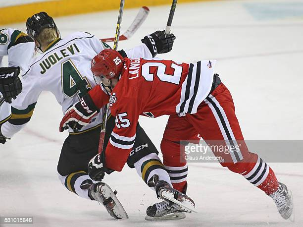 Olli Juolevi of the London Knights is knocked down by Kyle Langdon of the Niagara IceDogs during Game Four of the OHL Championship final for the...