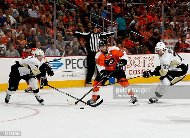 Olli Maatta and Evgeni Malkin of the Pittsburgh Penguins close in on Claude Giroux of the Philadelphia Flyers at the Wells Fargo Center on October 17...