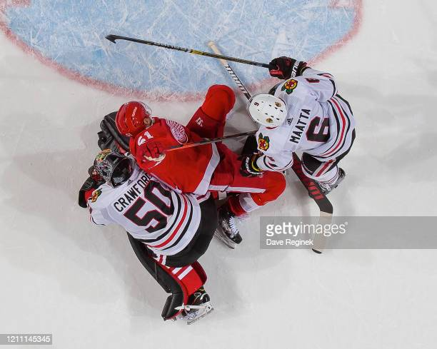 Olli Maatta of the Chicago Blackhawks pushes Valtteri Filppula of the Detroit Red Wings into Corey Crawford of the Blackhawks during an NHL game at...