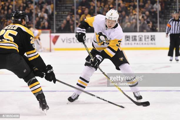 Olli Maatta of the Pittsburgh Penguins skates against Brandon Calro of the Boston Bruins at the TD Garden on November 24 2017 in Boston Massachusetts