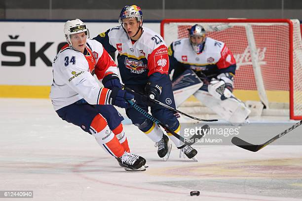 Olli Palola of Vaxjo and Dominik Kahun of Munich during the Champions Hockey League Round of 32 match between Red Bull Munich and Vaxjo Lakers at...