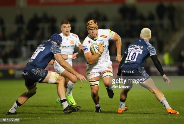 Ollie Atkins of Exeter Chiefs is tackled by Bryn Evans and James OConnor of Sale Sharks during the Aviva Premiership match between Sale Sharks and...