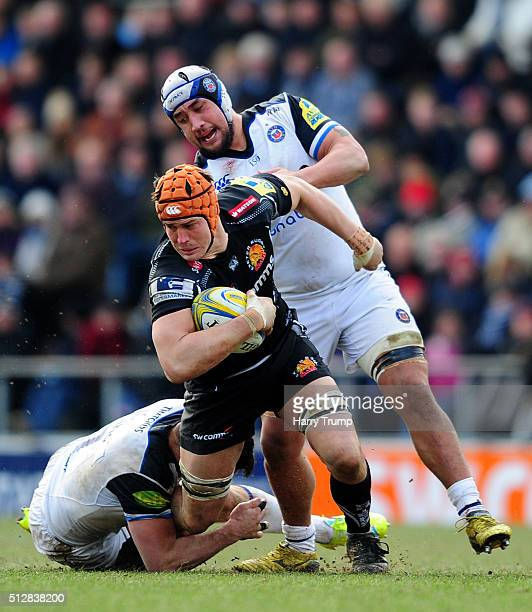Ollie Atkins of Exeter Chiefs is tackled by Francois Louw of Bath Rugby and Leroy Houston of Bath Rugby during the Aviva Premiership match between...