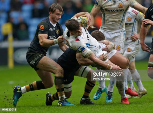 Ollie Devoto of Exeter Chiefs tackled by Josh Bassett and Thomas Young of Wasps during the Aviva Premiership match between Wasps and Exeter Chiefs at...