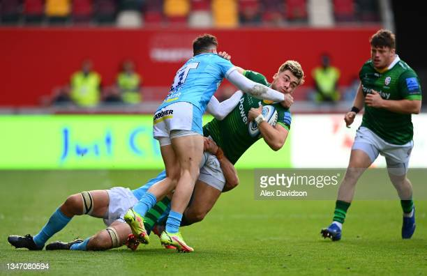 Ollie Hassell-Collins of London Irish is tackled by Jonny May and Lewis Ludlow of Gloucester during the Gallagher Premiership Rugby match between...