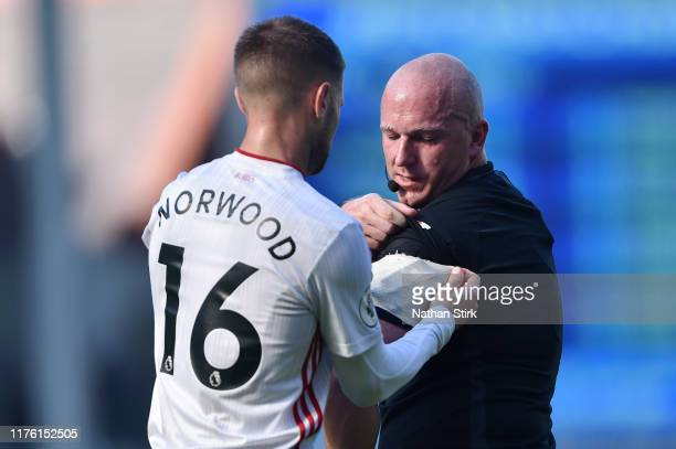 Ollie Norwood of Sheffield United assists referee Simon Hooper during the Premier League match between Everton FC and Sheffield United at Goodison...