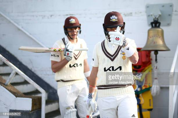 Ollie Pope and Jamie Smith of Surrey make their way to the field to open the evening session during day one of the Pre-season Friendly between Surrey...