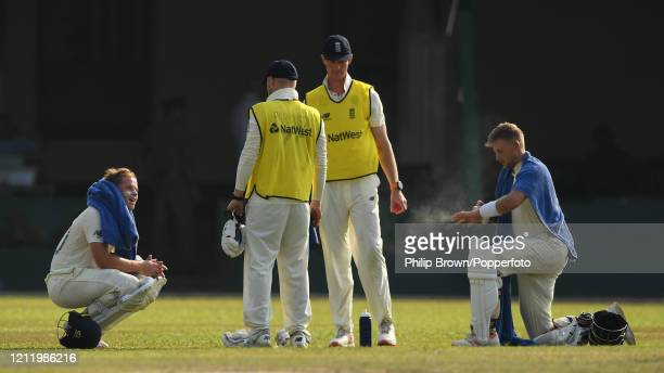 Ollie Pope and Joe Root of England have a break as Matt Parkinson and Keaton Jennings supply drinks towels and spray during the match between a Sri...