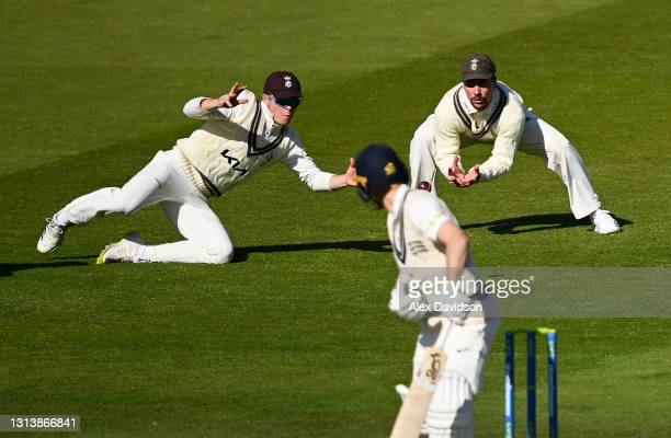 Ollie Pope and Rory Burns of Surrey drop a catch off Robbie White of Middlesex during Day One of the LV=Insurance County Championship match between...