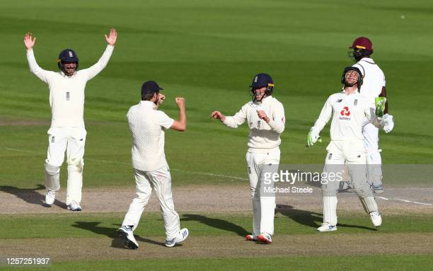Ollie Pope of England celebrates with Chris Woakes after taking the catch of Kemar Roach of West Indies to win the match during Day Five of the 2nd...