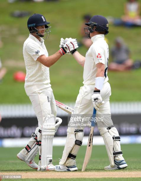 Ollie Pope of England shakes hands with captain Joe Root after reaching his half century during day 4 of the second Test match between New Zealand...