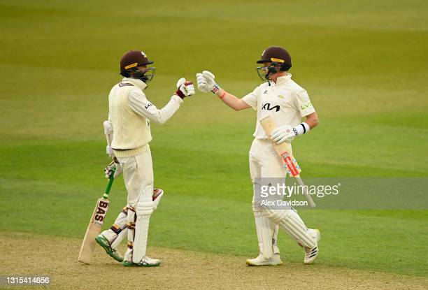 Ollie Pope of Surrey celebrates reaching his century with Hashim Amla during Day Two of the LV= Insurance County Championship match between Surrey...
