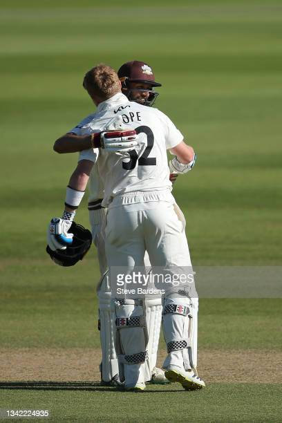 Ollie Pope of Surrey celebrates reaching his century with Hashim Amla on day four during the LV= Insurance County Championship match between Surrey...