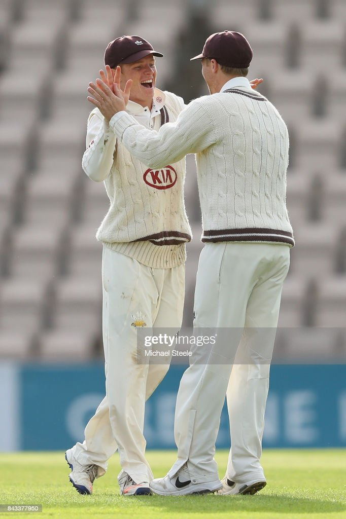Ollie Pope (L) of Surrey celebrates with Gareth Batty after taking a catch off the bowling of Rikki Clarke to dismiss Liam Dawson during day two of the Specsavers County Championship Division One match between Hampshire and Surrey at the Ageas Bowl on September 6, 2017 in Southampton, England.