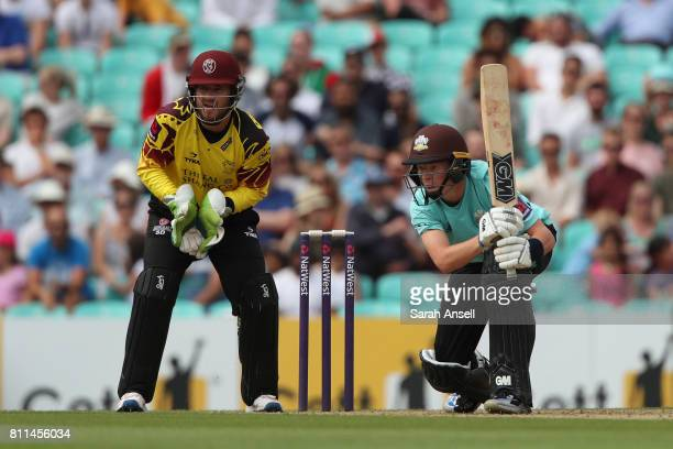 Ollie Pope of Surrey hits out as Somerset wicket keeper Steven Davies looks on during the NatWest T20 Blast match at The Kia Oval on July 9 2017 in...