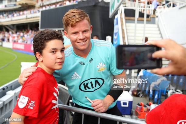 Ollie Pope of Surrey poses for a photo with a fan prior to the Vitality Blast match between Surrey and Glamorgan at The Kia Oval on July 25, 2019 in...