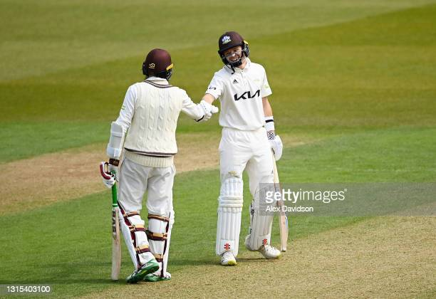 Ollie Pope of Surrey punches gloves with Hashim Amla during Day Two of the LV= Insurance County Championship match between Surrey and Hampshire at...