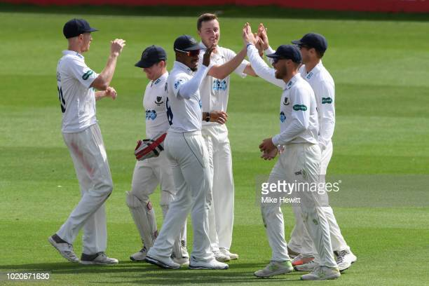 Umpire Graham Lloyd signals a six as bowler Matthew Critchley of Derbyshire trudges back to his mark during the Specsavers County Championship...
