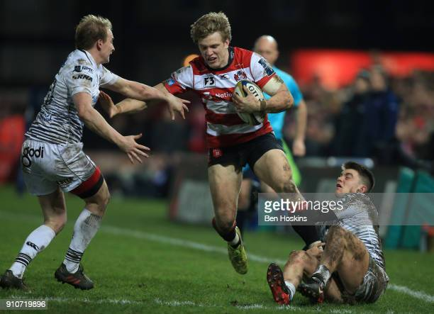 Ollie Thorley of Gloucester is tackled by Luke Price and Reuben MorganWilliams of Ospreys during the AngloWelsh Cup match between Gloucester Rugby...