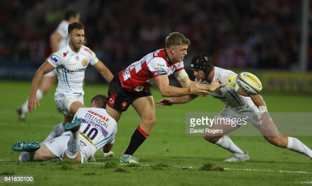 Ollie Thorley of Gloucester off loads the ball as Gareth Steenson tackles during the Aviva Premiership match between Gloucester Rugby and Exeter...