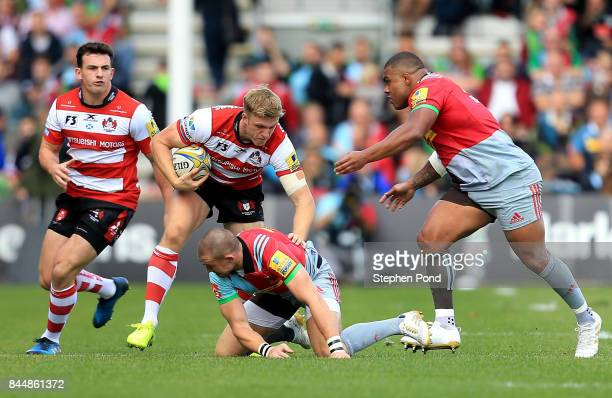 Ollie Thorley of Gloucester Rugby is tackled by Mike Brown and Kyle Sinckler of Harlequins during the Aviva Premiership match between Harlequins and...