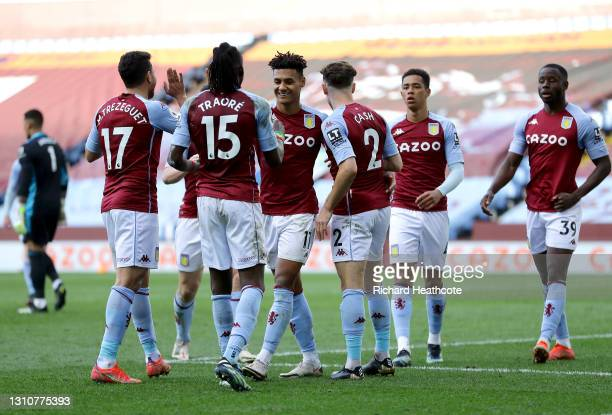 Ollie Watkins of Aston Villa celebrates with team mates Matty Cash and Bertrand Traore after scoring their side's third goal during the Premier...