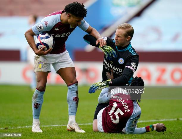 Ollie Watkins of Aston Villa clashes with Kasper Schmeichel of Leicester City as Bertrand Traore of Aston Villa scores their side's first goal during...