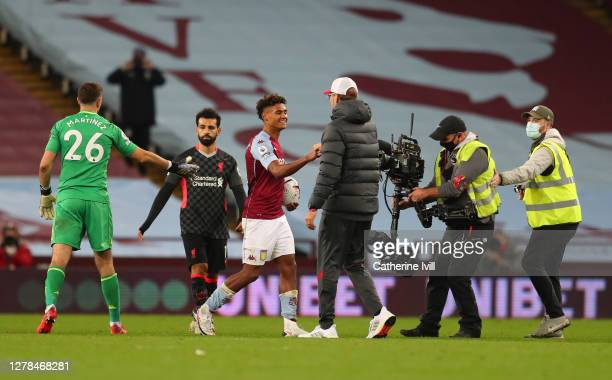 Ollie Watkins of Aston Villa holds the match ball after scoring a Hat-trick as Jurgen Klopp, Manager of Liverpool shakes his hand after the Premier...