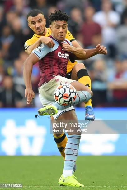 Ollie Watkins of Aston Villa is challenged by Romain Saiss of Wolverhampton Wanderers during the Premier League match between Aston Villa and...